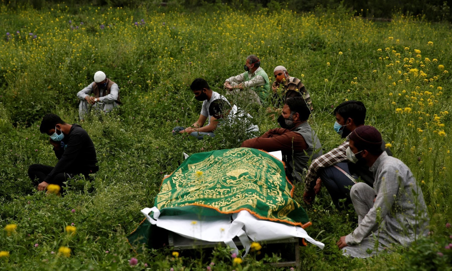 Relatives sit next to the body of a man who died due to Covid-19, as they wait for a grave to be prepared for his burial at a graveyard on the outskirts of Srinagar, May 4. — Reuters