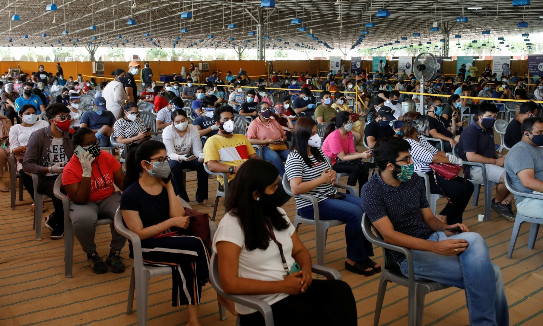 People wearing protective face masks wait to receive a dose of COVISHIELD, a coronavirus vaccine manufactured by Serum Institute of India, at a vaccination centre in New Delhi, India, May 4. — Reuters