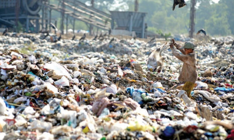 A boy looks for recyclable items at the landfill site in I-12. — White Star
