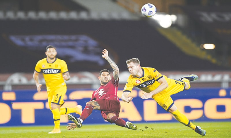 TURIN: Players of Torino and Parma fight for the ball during their Serie A match at the Olimpico Grande Torino Stadium.—AP
