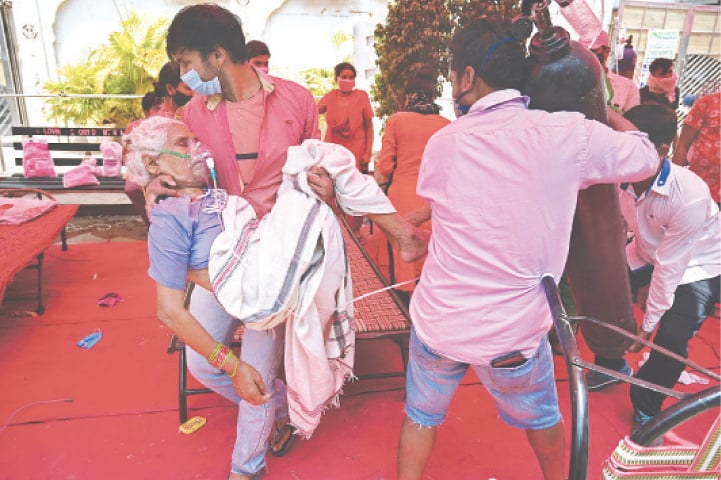 GHAZIABAD: A family member carries a patient breathing with the help of oxygen provided by a Gurdwara under a tent installed along a road.—AFP