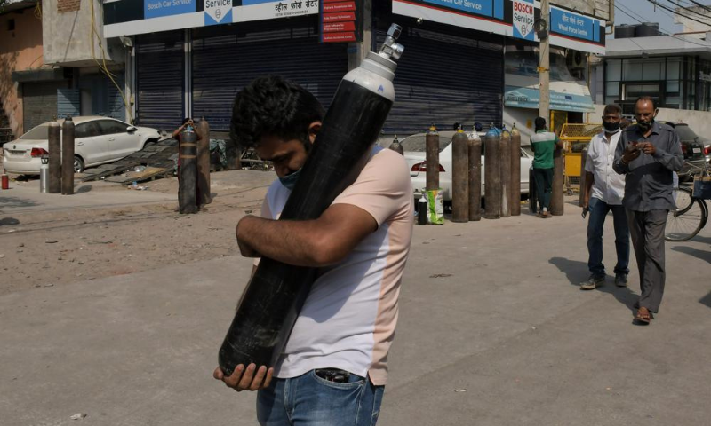 A man walks carrying a refilled cylinder as family members of Covid-19 patients wait in queue to refill their oxygen cylinders at Mayapuri area in New Delhi, India on Monday. — AP