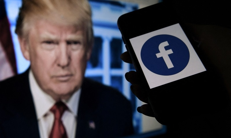 In this file photo illustration, a phone screen displays a Facebook logo with the official portrait of former US president Donald Trump in the background, on May 4, 2021, in Arlington, Virginia. — AFP