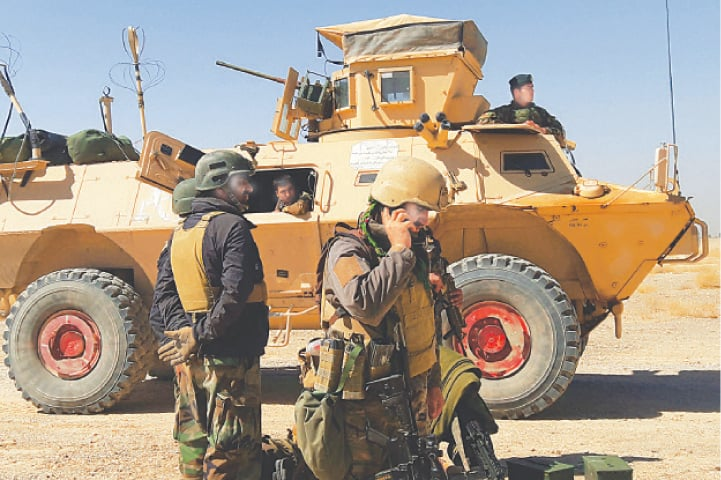 LASHKAR GAH: Afghan security personnel stand near an armoured vehicle on the outskirts of the capital of Helmand province on Wednesday.—AFP