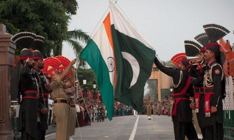 Pakistani and Indian soldiers lower the flags of their countries during a daily ceremony at the Wagah border. — AFP/File