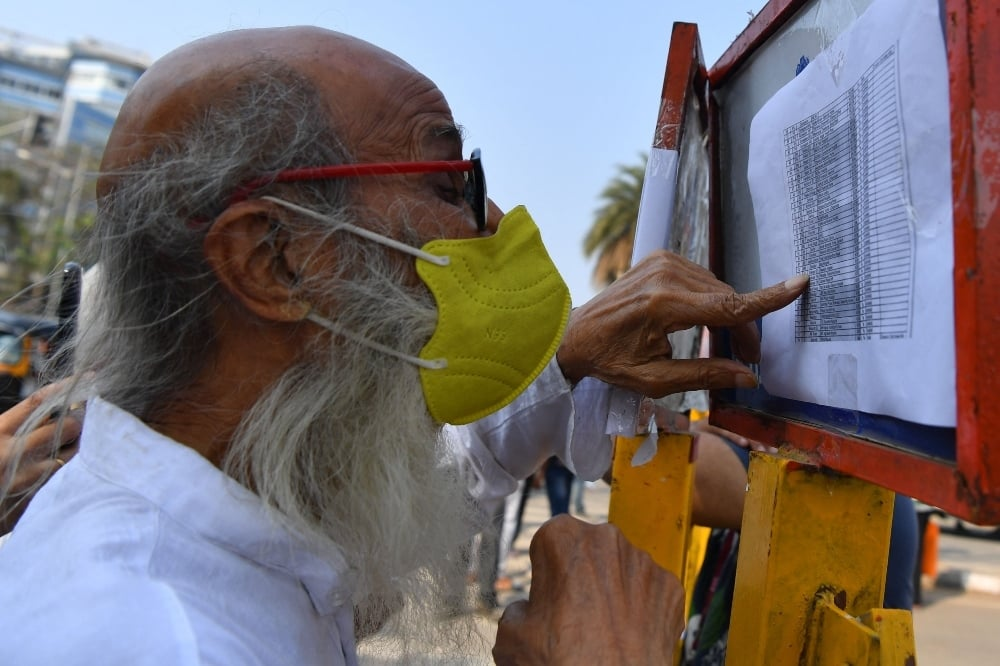 A man checks a list of vaccination centres after being turn down for his scheduled second vaccine dose due to stock shortages in Mumbai on May 6. — AFP