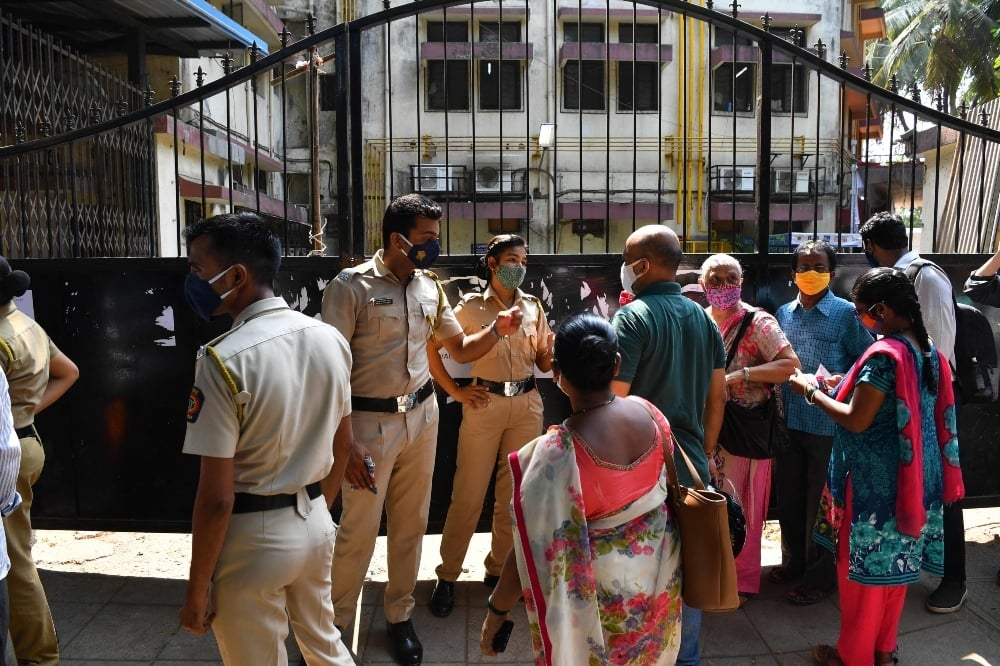 Police officer talk to people standing outside a closed vaccination centre due stock shortages of Covid-19 coronavirus vaccines in Mumbai on May 6. — AFP
