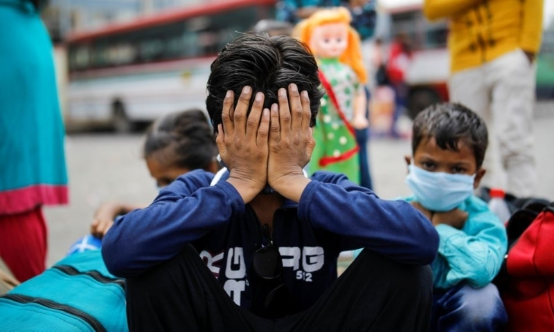 Children of migrant workers sit at a bus station, as they wait to board a bus to return to their villages, after the Delhi government ordered a six-day lockdown to limit the spread of the coronavirus disease, in Ghaziabad on the outskirts of New Delhi, India, April 20. — Reuters