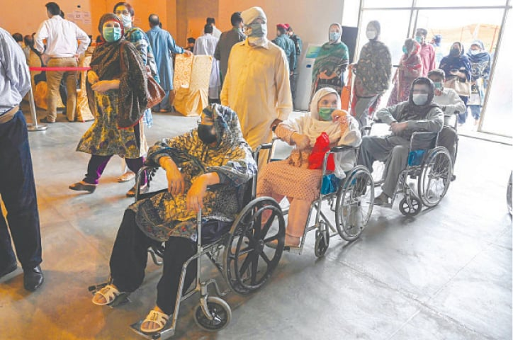 LAHORE: People wait to get a dose of Sinopharm at a vaccination centre on Thursday.—AFP