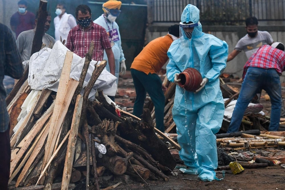 A man wearing a protective suit performs the last rites before the cremation of his relative who died of Covid-19 at a cremation ground in New Delhi on May 6. — AFP