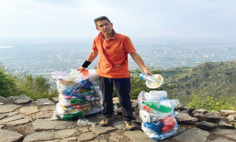 British Ambassador Christian Turner holds bags of trash collected from the Margalla Hills on Friday.