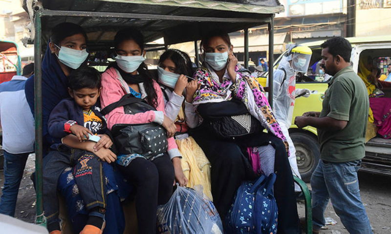 A family wearing facemasks as a preventive measure against the Covid-19 coronavirus sit in a three wheeler vehicle along a street, in Karachi. — AFP/File