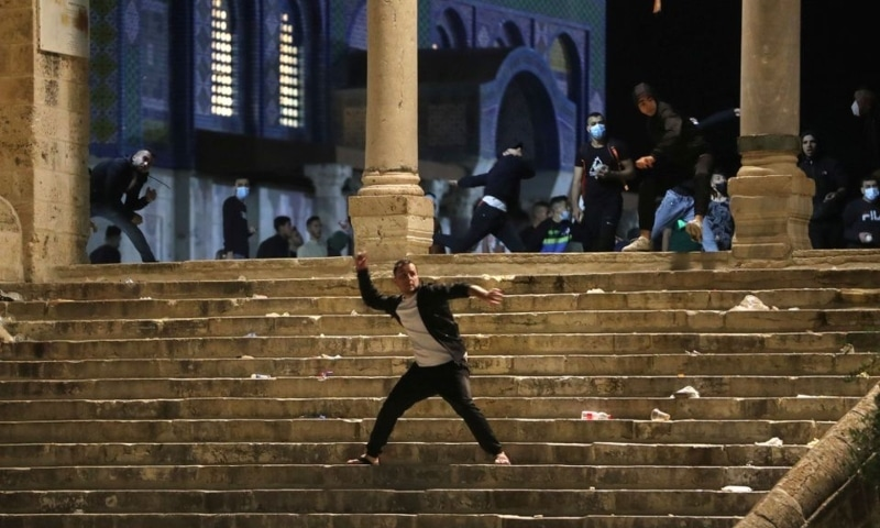 A Palestinian hurls stones at Israeli police during clashes at the compound that houses Al Aqsa Mosque amid tension over the possible eviction of several Palestinian families from homes on land claimed by Jewish settlers in the Sheikh Jarrah neighbourhood, in Jerusalem's Old City on Friday. — Reuters