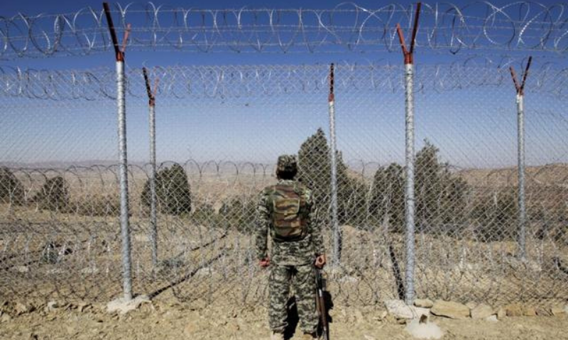 A Pakistani soldier stands guard along the fence at an outpost on the Pak-Afghan border. — Reuters/File