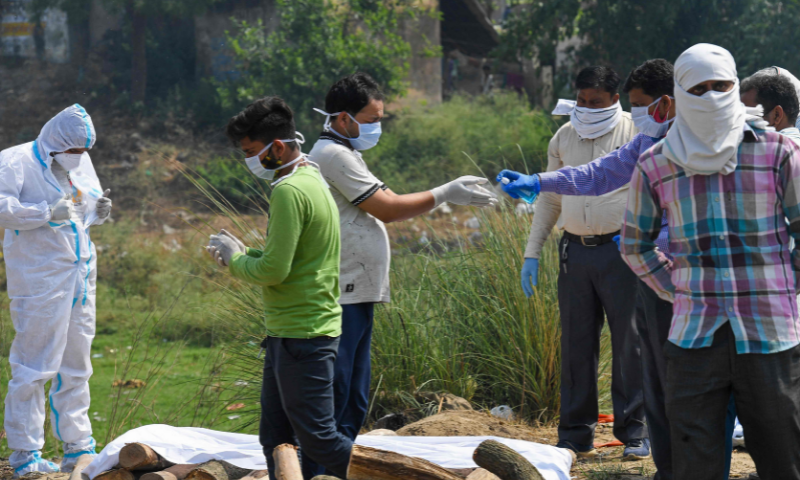 Relatives prepare to cremate the body of their loved one who died due to Covid-19 at a crematorium in Moradabad, India. — AFP/File