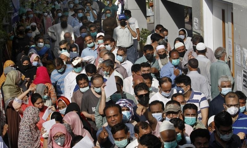 People stand in queues while they wait their turn to receive the first shot of the Sinopharm Covid-19 vaccine at a vaccination centre in Karachi, May 8. — AP