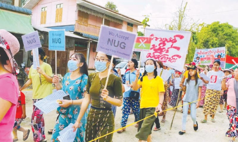 Protesters marching with placards supporting the opposition National Unity Government (NUG) during a demonstration against the military coup in Hpakant in Myanmar's Kachin state. — AFP