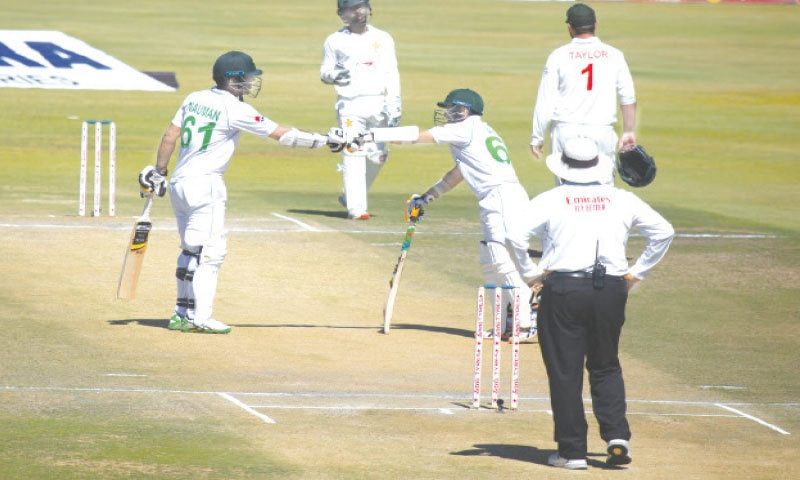 HARARE: Pakistan opener Abid Ali (R) and batting partner Nauman Ali touch gloves during the second Test against Zimbabwe at the Harare Sports Club on Saturday. — AP