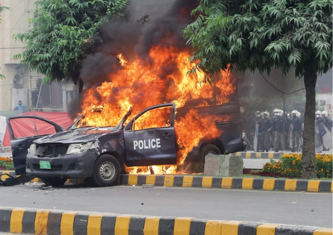 A police vehicle is seen in flames after lawyers set it on fire when they attacked the Punjab Institute of Cardiology in December 2019 | Aun Jafri/White Star