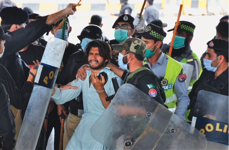 Police officers arrest a TLP activist in Peshawar during a protest following the arrest of party chief Saad Hussain Rizvi | Shahbaz Butt/White Star