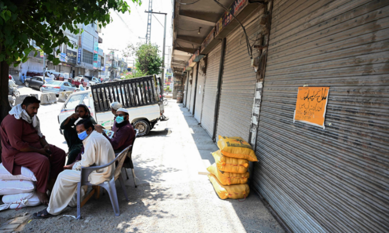 Shopkeepers sit along a closed market after a shutdown was imposed in a bid to prevent a surge in Covid-19 cases during Eid in Rawalpindi on Saturday. — AFP