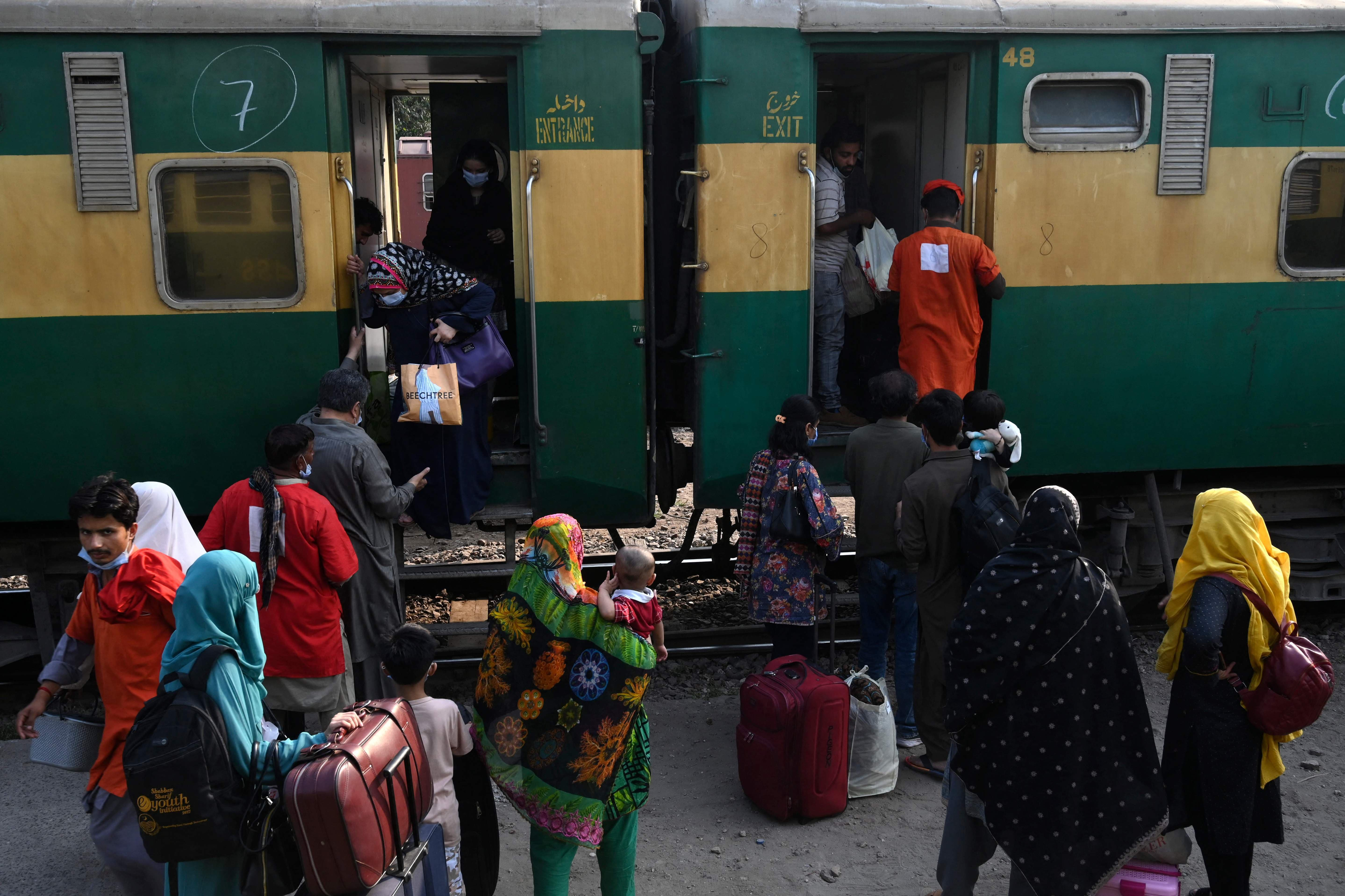 Passengers board a train to their hometowns during Ramazan in Lahore on Saturday. — AFP