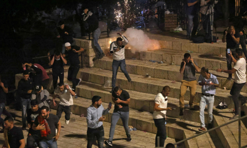 Palestinian protesters run from stun grenades fired by Israeli security forces outside the Damascus Gate in Jerusalem's Old City on Saturday. — AFP