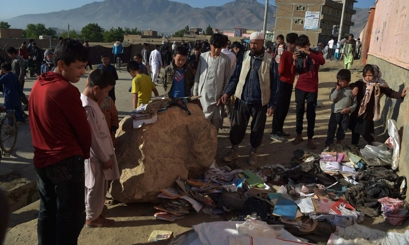 Onlookers stand next to a pile of backpacks and books of victims following multiple blasts outside a girls' school in Dasht-e-Barchi on the outskirts of Kabul, Afghanistan on Sunday. — AFP