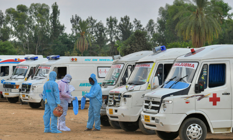 Family members and relatives wearing protective gear stand next to ambulances carrying the bodies of victims who died of Covid-19 at an open-air crematorium on the outskirts of Bangalore. — AFP