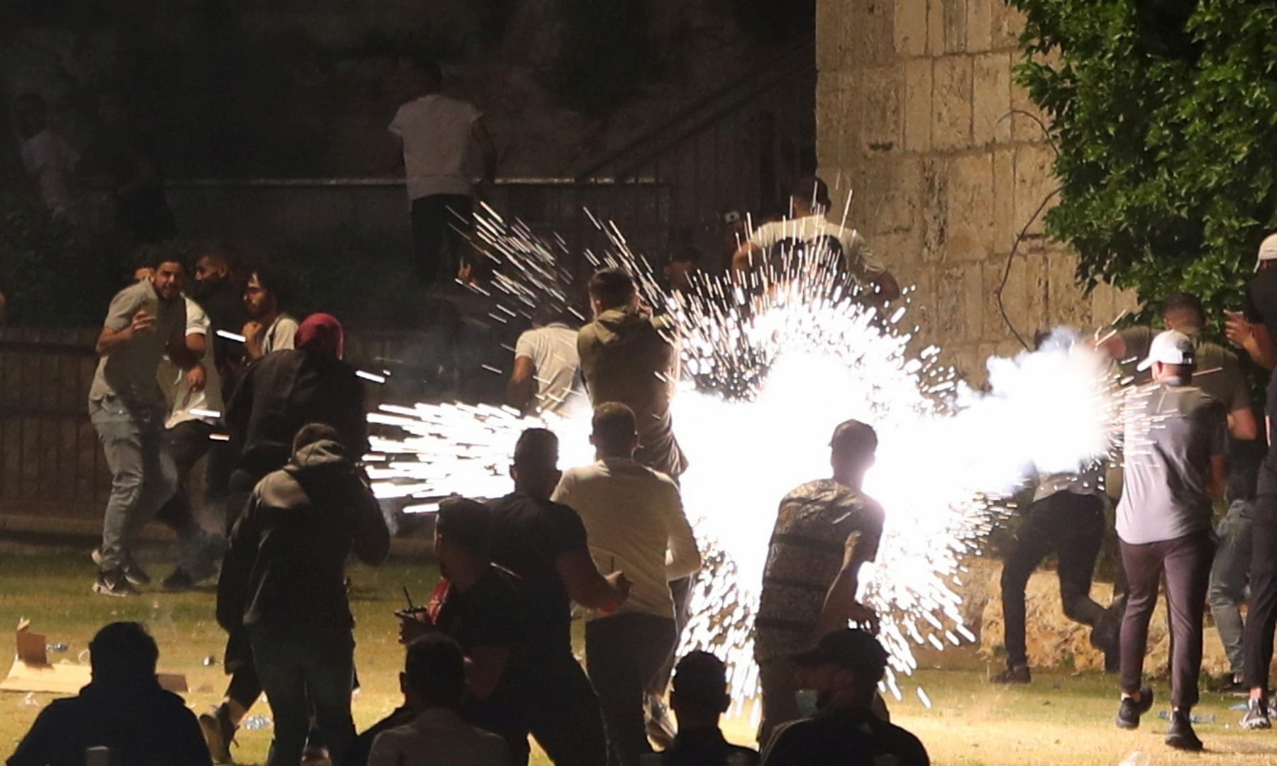 Palestinians react as Israeli police fire a stun grenade during clashes on Laylat al-Qadr at Jerusalem's Old City, May 8. — Reuters