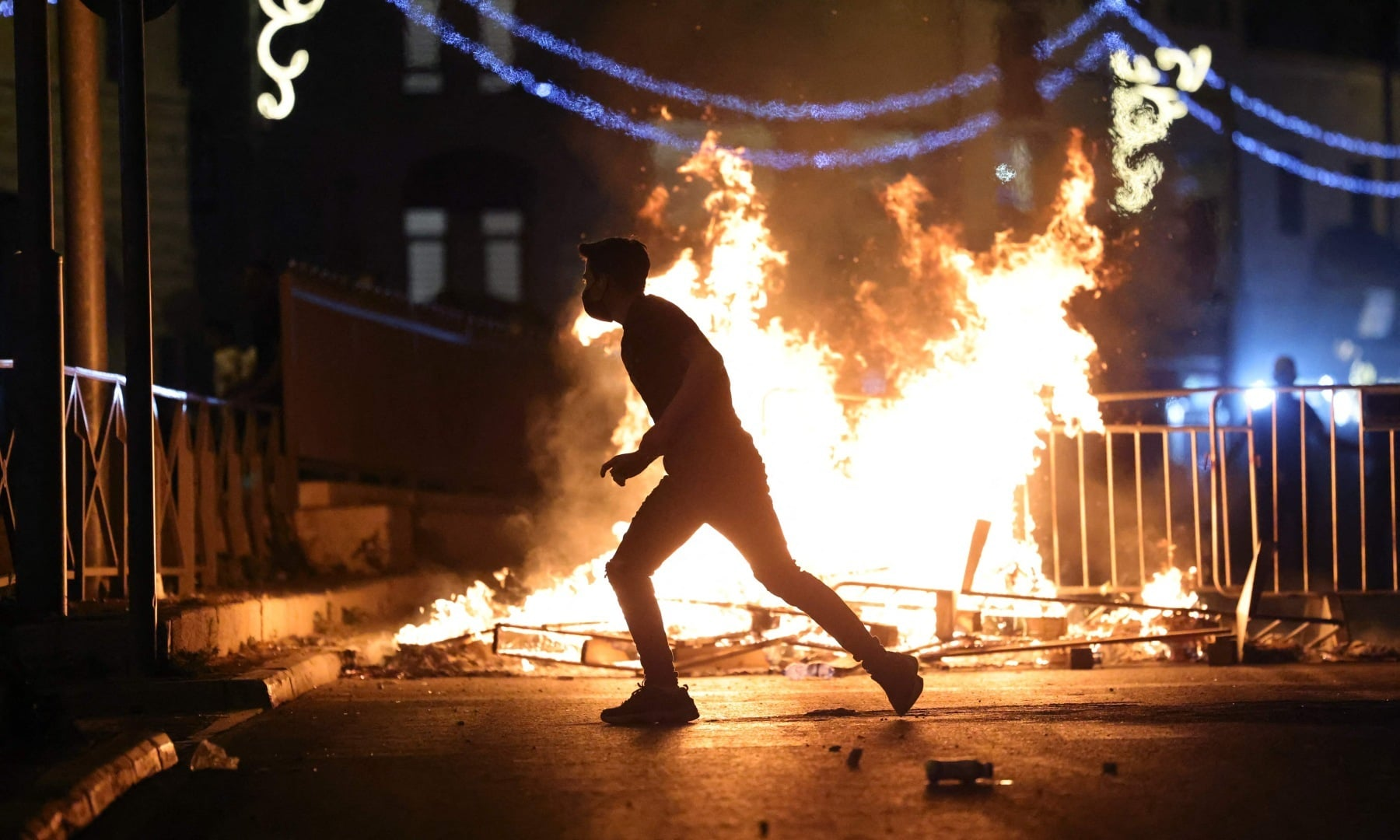 A Palestinian protester runs near a burning barricade in Jerusalem's Old City on May 8. — AFP