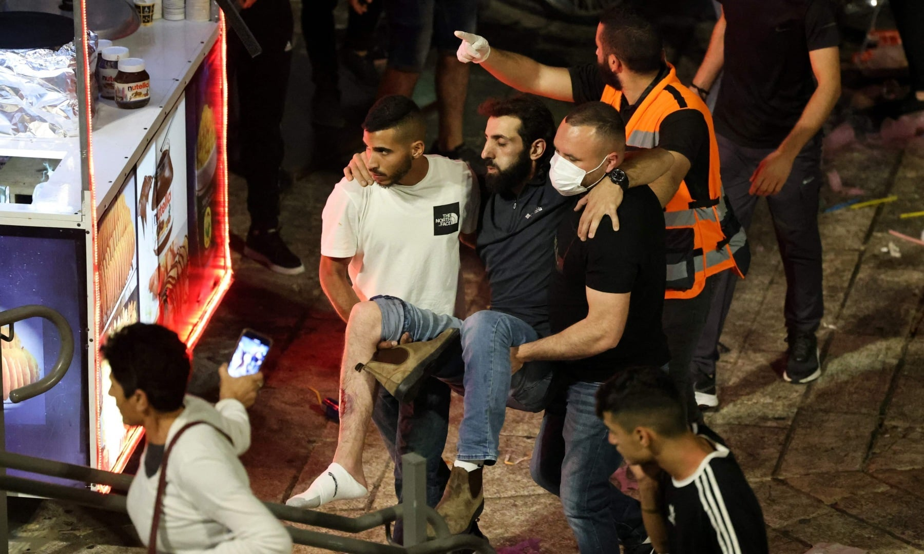 Palestinians assist a wounded protester amid clashes with Israeli security forces outside the Damascus Gate in Jerusalem's Old City on May 8. — AFP