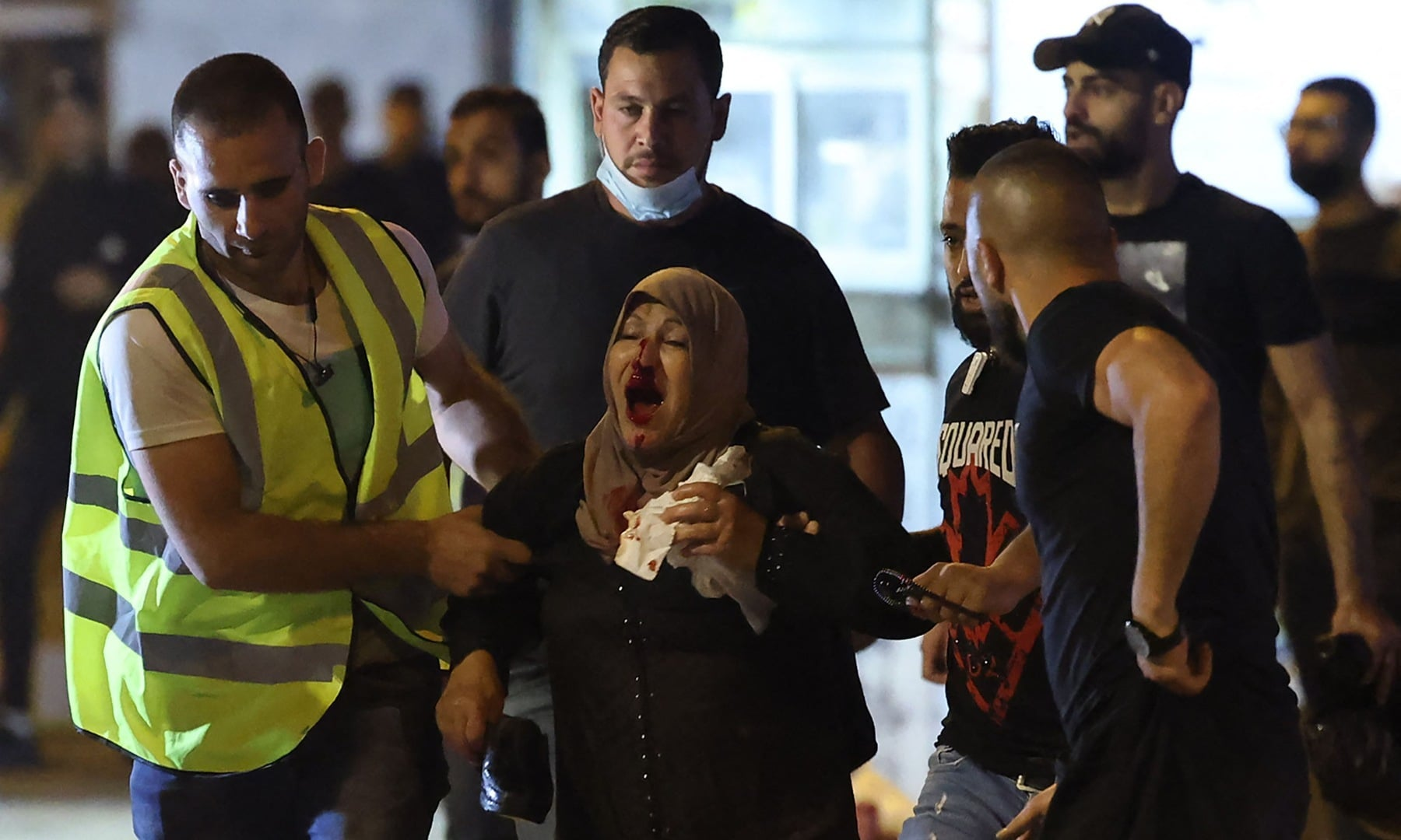 Palestinians assist a wounded woman amid clashes with Israeli security forces in Jerusalem's Old City on May 8. — AFP