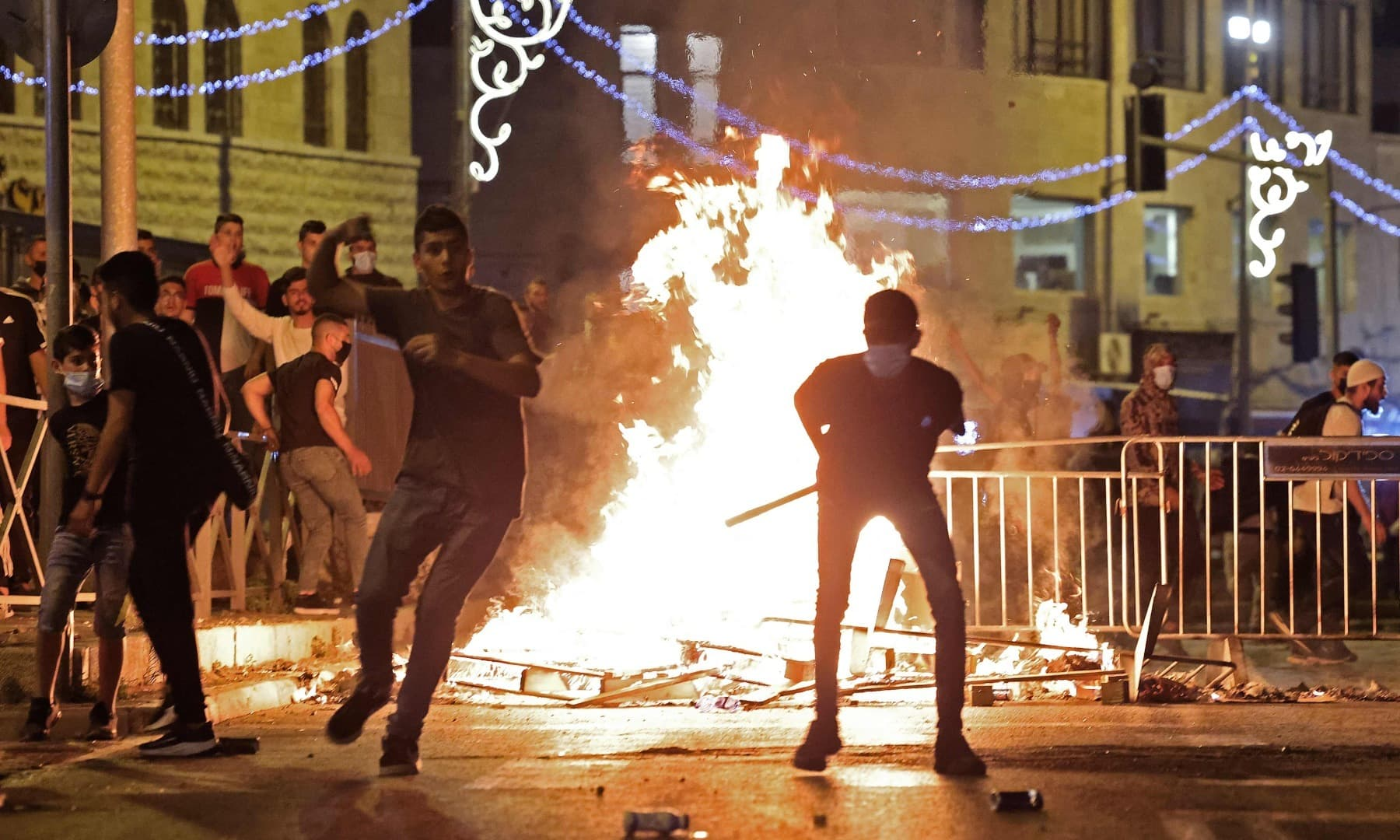 Palestinian protesters hurl stones at Israeli security forces amid clashes in Jerusalem's Old City on May 8. — AFP