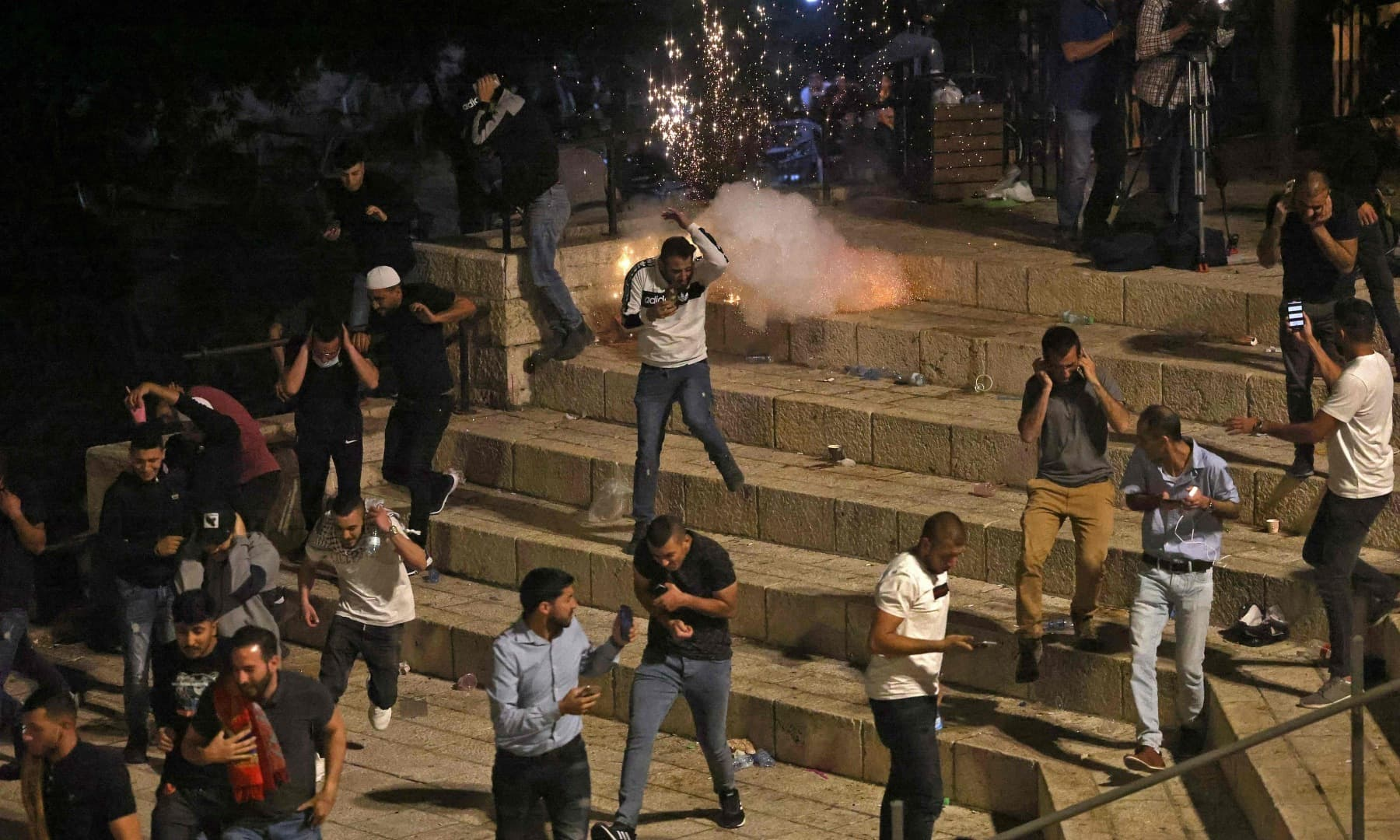 Palestinian protesters run from stun grenades fired by Israeli security forces outside the Damascus Gate in Jerusalem's Old City on May 8, 2021. — AFP