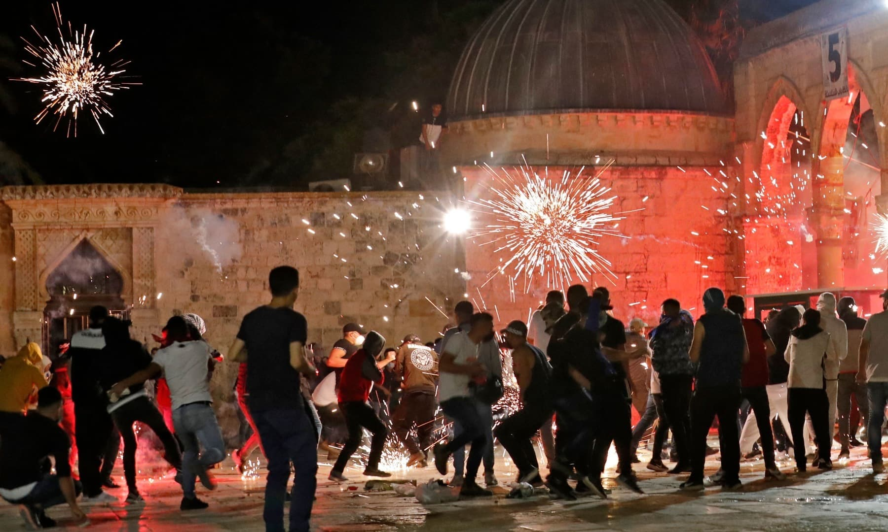 Stun grenades burst in the air amid clashes between Palestinian protesters and Israeli security forces at the Al-Aqsa mosque compound in Jerusalem, on May 7, 2021. — AFP
