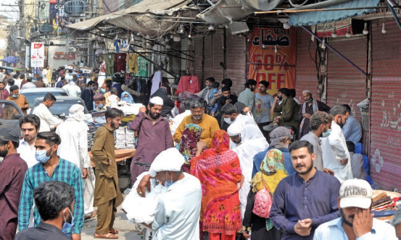 Despite lockdown, shopkeepers can be seen selling their goods outside their closed shops in Rawalpindi's Raja Bazaar on Sunday. — Photo by Mohammad Asim