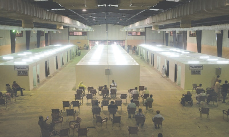 KARACHI: People wait for their turn at the Expo Centre, which has been converted into a Covid-19 vaccination facility. A large number of people turned up to get themselves inoculated against the disease on Sunday.—Shakeel Adil / White Star