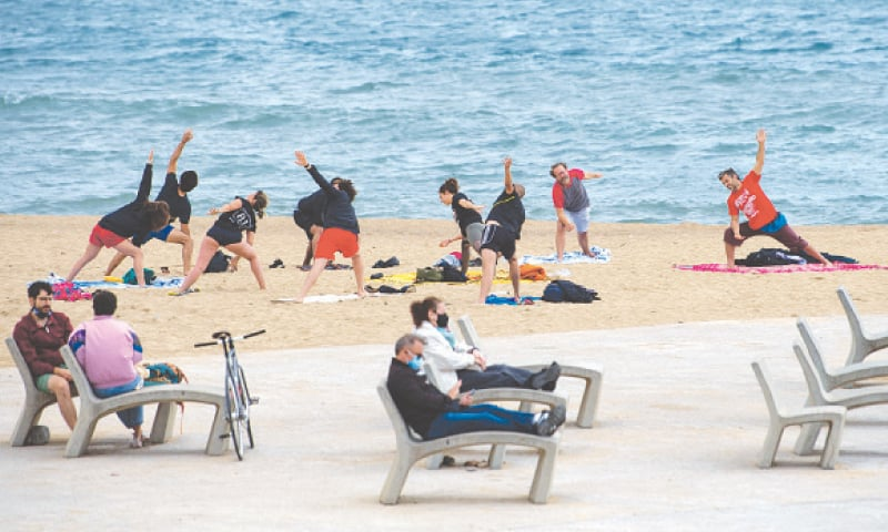 SPANIARDS practise yoga at the beach in Barcelona on Sunday after the lifting of coronavirus emergency.—AFP