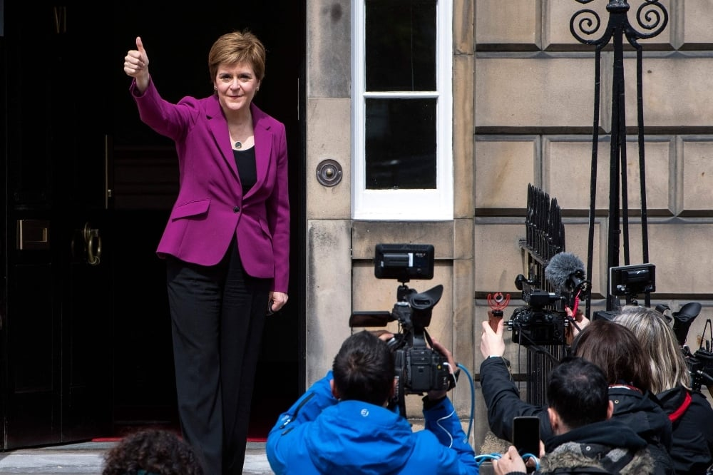 Scotland's First Minister and leader of the Scottish National Party (SNP), Nicola Sturgeon gives a thumbs-up on the steps of her official residence Bute House in Edinburgh on May 9. — AFP
