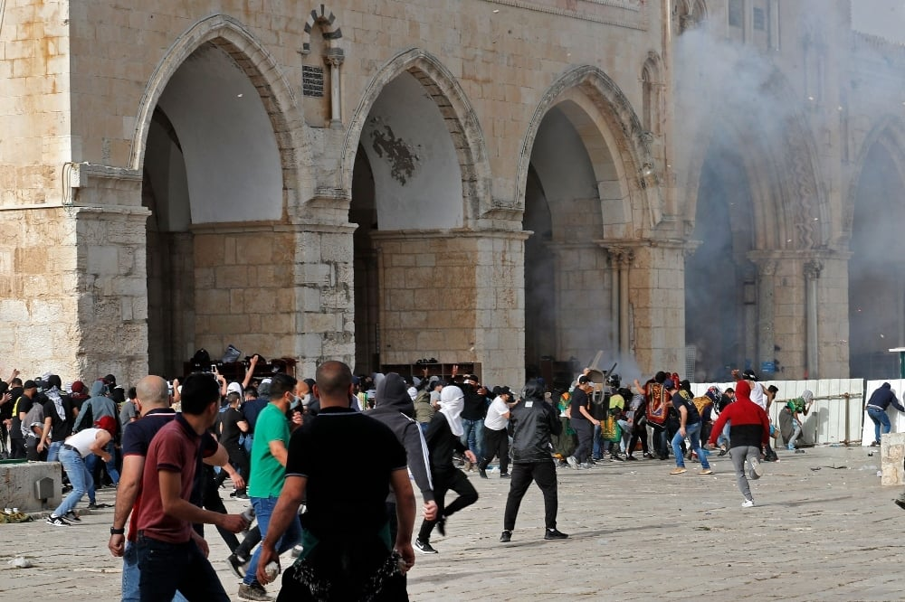 Palestinian protesters and Israeli security forces at Jerusalem's Al Aqsa mosque compound on May 10. — AFP