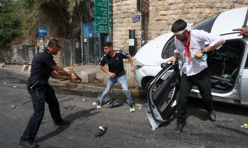 An Israeli police officer stands with pistol pointed at a Palestinian man, centre, next to a Jewish driver who was allegedly attacked by Palestinian protesters near Jerusalem's Old City, Monday, May 10. — AP