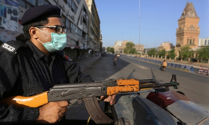 A police officer stands guard in a business district to ensure a lockdown to help control the spread of the coronavirus in Karachi, Sunday, May 9, 2021. — AP