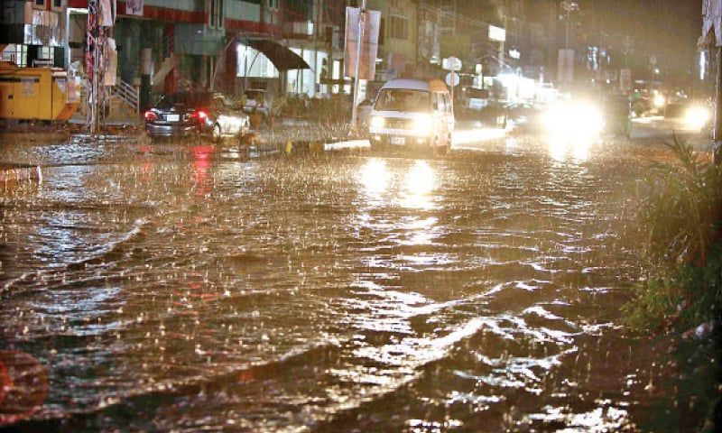 Vehicles pass through a flooded road in Ghauri Town during heavy rain in Islamabad on Monday night. — APP