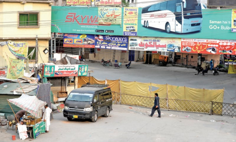 The district administration has closed the entrance to Bank Road in Saddar, a policeman reprimands a shopkeeper for selling garments despite the lockdown in Bara Market, banners have been hung up on poles on the overhead bridge at Chandni Chowk to create awareness of the precautionary measures against Covid-19 while the bus terminal at Faizabad lies deserted on Monday. — Photos by Mohammad Asim