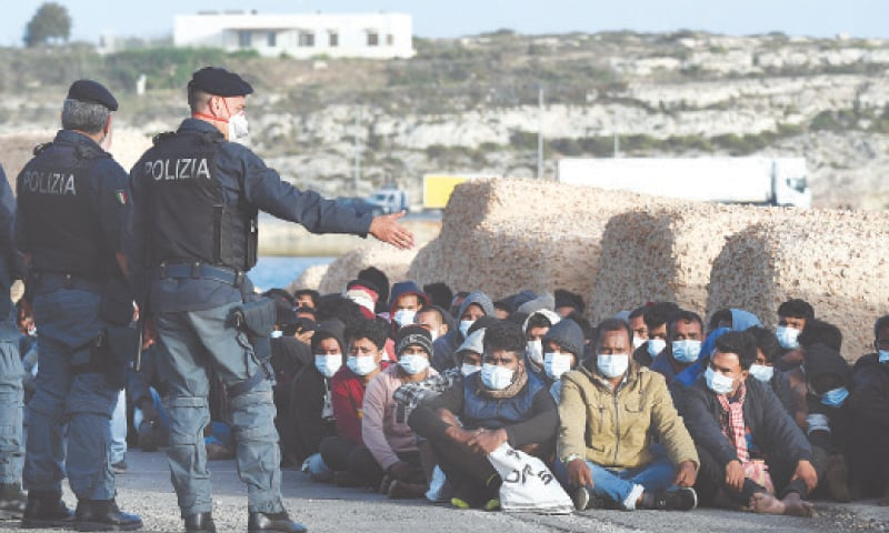 MIGRANTS wearing face masks to curb the spread of Covid-19 sit at a pier as Italian police officers stand by, on the Sicilian island of Lampedusa, southern Italy, on Monday.—AP