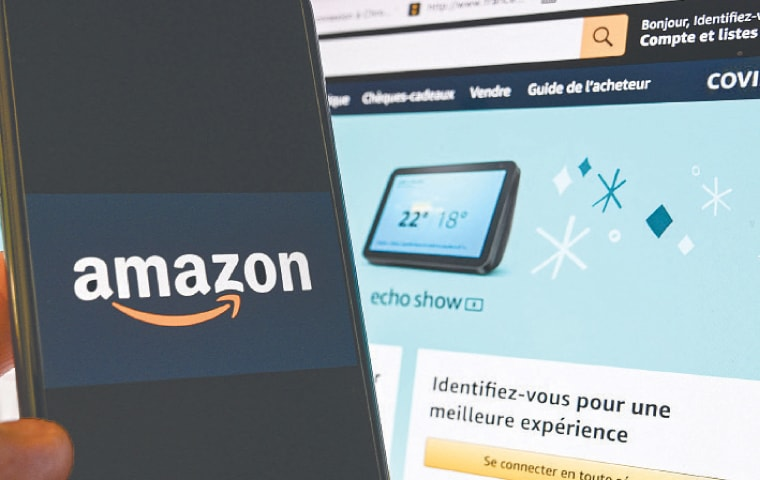 A smartphone showing an Amazon logo, in front of a computer screen displaying the home page of Amazon France sales website.—AFP