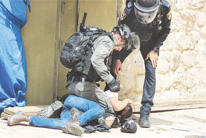 ISRAELI police detain a Palestinian during violence at the compound that houses Al Aqsa mosque on Monday.—Reuters