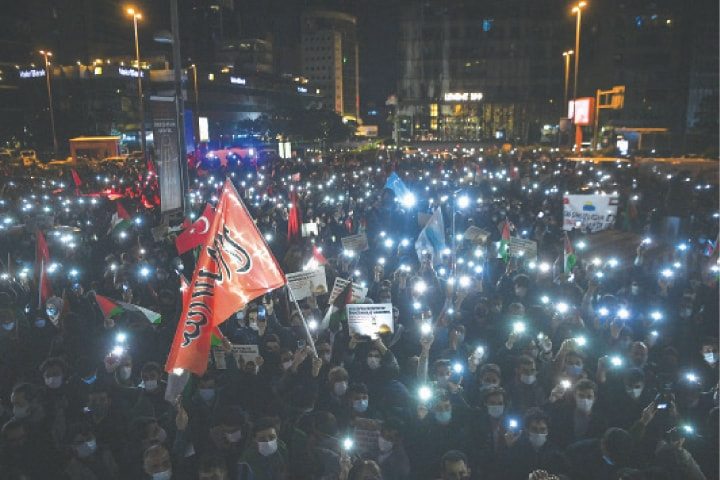 Istanbul: Protesters hold up their phones with the light on, alongside Palestine and Turkish national flags, during a demonstration against Israel in front of its consulate in Istanbul.—AFP