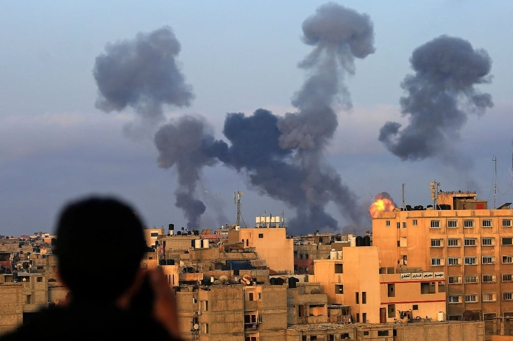 A Palestinian boy watches smoke billowing from targets during Israeli airstrikes on the southern Gaza region of Khan Yunis, controlled by the Hamas movement, on May 11. — AFP
